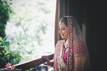 Bride in Shades of Pink Looking out of Window