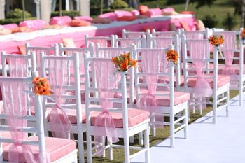 Chair backs decorated with pink ribbons and a bunch of flowers.
