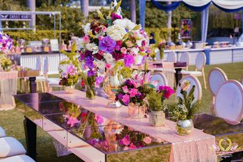 Long glass table decorated with floral vases.