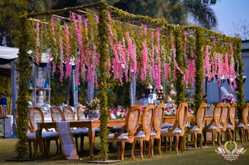 Outdoor dinner table seating with floral ceilings.