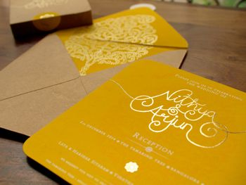 Photo of yellow and brown invitation card with tree of life motif