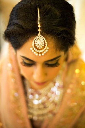 Bride Wearing Diamond and Pearl Maangtikka in Focus