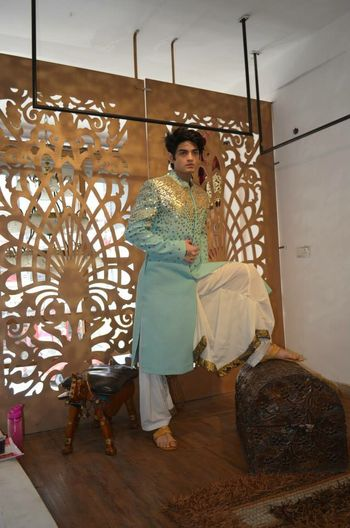 Photo of pastel blue sherwani with gold work and white dhoti