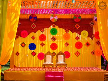 Mehndi decor with yellow backdrop decorated with paper flowers and kites.