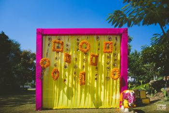 Mehendi Photo Booth idea with yellow backdrop and genda pool frames