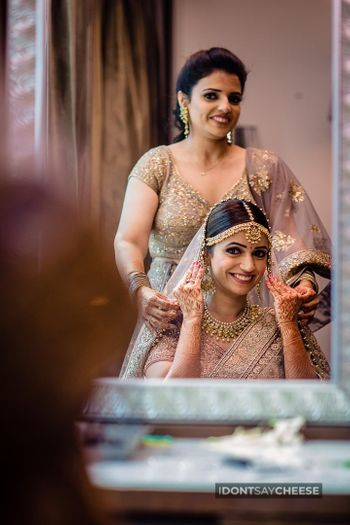 bride with her sister dupatta placing on head shot