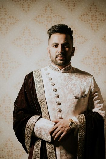 off white and gold groom sherwani with asymmetric buttons