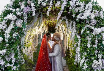 couple kissing against heavy floral mandap decor
