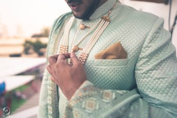 offbeat groom sherwani with pearl necklace