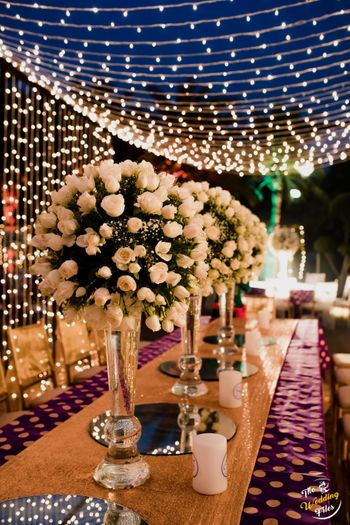 Tall floral vases used as table centrepieces with fairy light in the backdrop.