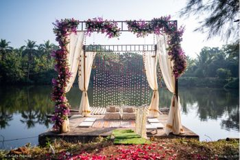Beachside mandap decor with drapes and flowers.