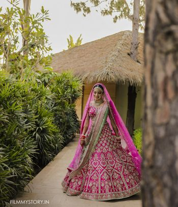 twirling bride in bright pink lehenga with green dupatta