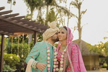 Photo of contrasting bride and groom in turquoise and bright pink
