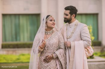 Photo of pastel bride and groom with unique dupatta