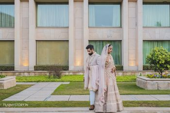 Photo of pastel bride and groom in matching light pink outfits