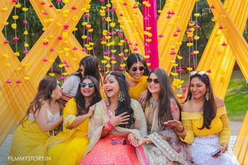 Photo of bride with her bridesmaids against yellow and pink backdrop