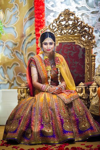Photo of Ombre shimmery mango yellow and purple lehenga with bride sitting on chair