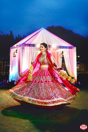 Bride Twirling in Deep Pink and Gold Wedding Lehenga