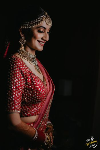 Candid shot of a smiling bride in a red lehenga.