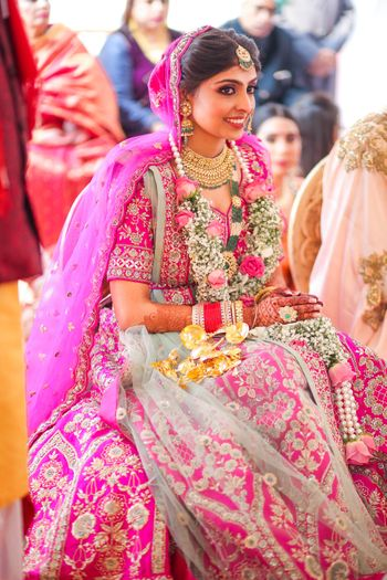 Bride dressed in a Fuschia pink lehenga on her wedding day.