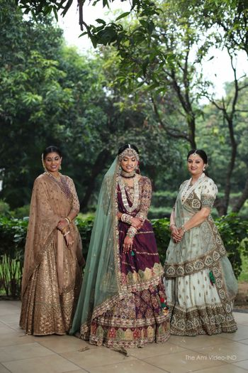 bride in unique lehenga with mother and her sister