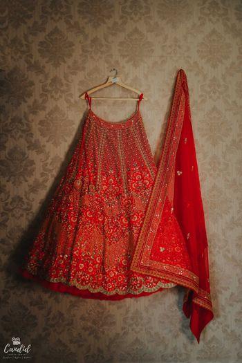 red bridal lehenga on hanger shot