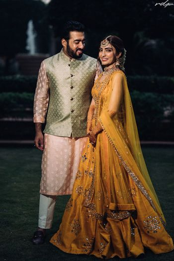 Candid shot of bride and groom dressed in yellow and pastel hues respectively.