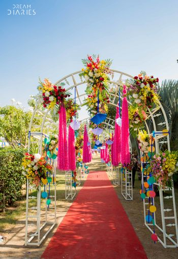A quirky archway entrance with floral arrangements and other fancy elements.