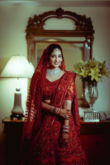 A bride dressed in monotone red lehenga