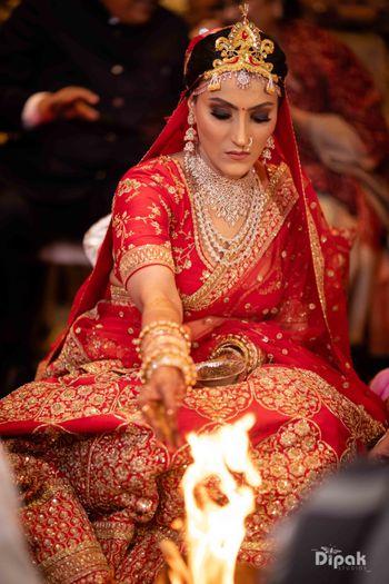 modern bengali bride in red and gold sabyasachi lehenga