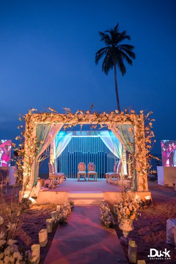 All white mandap decorated with flowers and foliage