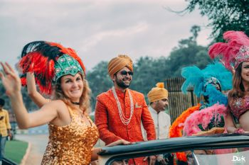 Groom entering in a car with dancers.