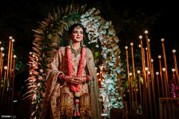Photo of bride in pastel lehenga designed by her mom