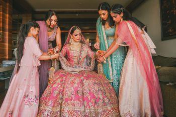 Photo of bridesmaids helping bride get ready