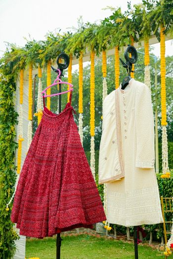 lehenga and sherwani on hanger next to each other
