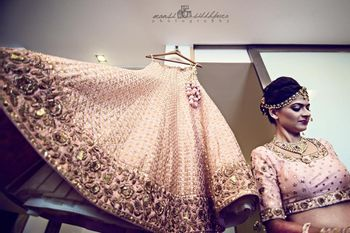 Bride Getting Ready with Light Pink Lehenga on Hanger
