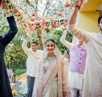Bridal entry under a phoolon ki chaadar.