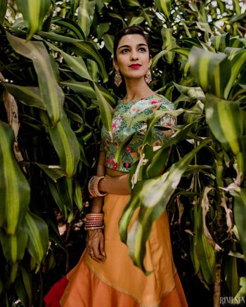 Photo of Bride wearing a printed crop top with a plain yellow skirt.