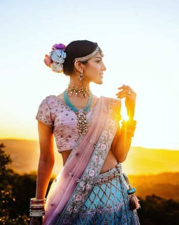 Photo of Candid shot of a bride dressed in a pink and blue lehenga.