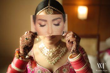 bridal makeup portrait with bride holding eye palette