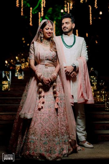 Photo of couple shot with bride in millennial pink lehenga with waistbelt