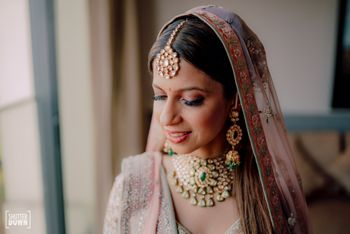 Photo of subtle bridal makeup with light pink lehenga with floral border