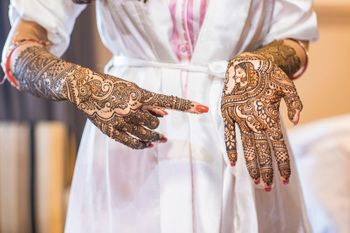 bride showing her portrait mehendi on one hand