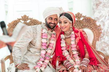 happy post wedding shot with pink jaimalas