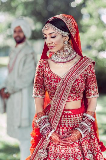 red sabyasachi lehenga with matching jewellery