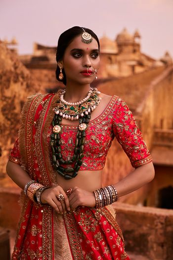 Photo of Strawberry Red Lehenga with Green Statement Jewellery