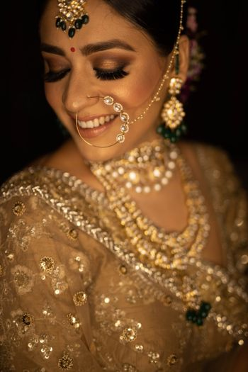 subtle bridal makeup with nude lip and gold lehenga