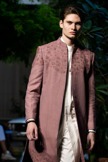 A dusty pink open sherwani with s white kurta for grooms.