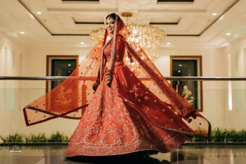 Twirling shot of a bride dressed in a red lehenga.