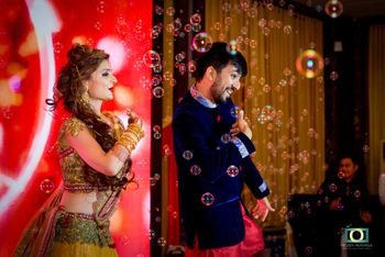 Photo of Guests Blowing Bubbles while Bride and Groom Perform